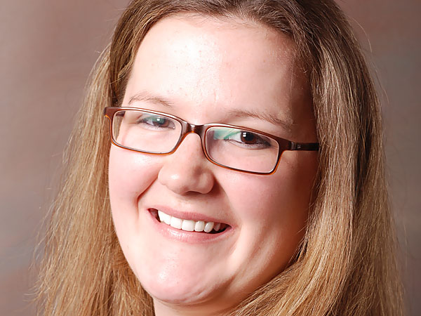 Bespectacled smiling woman with visibly better teeth after dental treatment at Petinge Dental